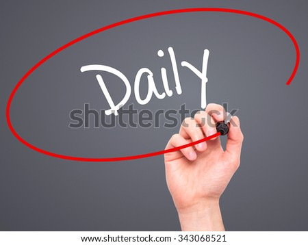 Man Hand writing Daily with black marker on visual screen. Isolated on grey. Business, technology, internet concept. Stock Photo