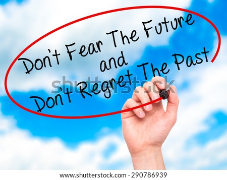 Man Hand writing Don't Fear The Future and Don't Regret The Past with black marker on visual screen. Isolated on sky. Life, technology, internet concept. Stock Image - stock photo