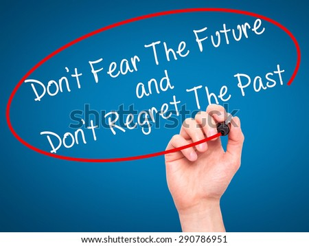 Man Hand writing Don't Fear The Future and Don't Regret The Past with black marker on visual screen. Isolated on blue. Life, technology, internet concept. Stock Image