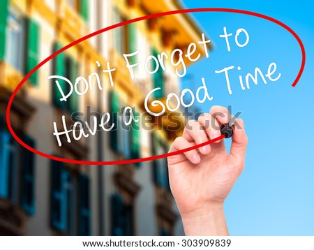 Man Hand writing Don't Forget to Have a Good Time with black marker on visual screen. Isolated on city. Business, technology, internet concept. Stock Photo - stock photo