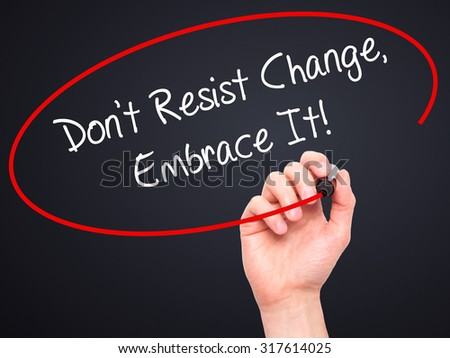 Man Hand writing Don't Resist Change, Embrace It! with black marker on visual screen. Isolated on black. Business, technology, internet concept. - stock photo