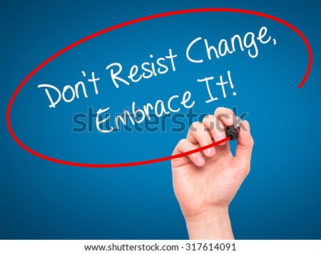 Man Hand writing Don't Resist Change, Embrace It! with black marker on visual screen. Isolated on blue. Business, technology, internet concept. - stock photo