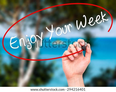 Man Hand writing Enjoy Your Week with black marker on visual screen. Isolated on nature. Business, technology, internet concept. Stock Photo - stock photo