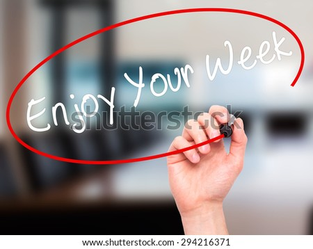 Man Hand writing Enjoy Your Week with black marker on visual screen. Isolated on office. Business, technology, internet concept. Stock Photo - stock photo