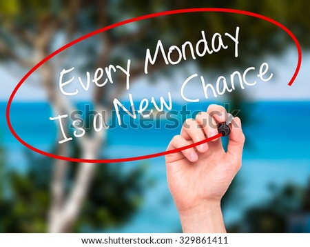 Man Hand writing Every Monday Is a New Chance with black marker on visual screen. Isolated on nature. Business, technology, internet concept. Stock Photo - stock photo