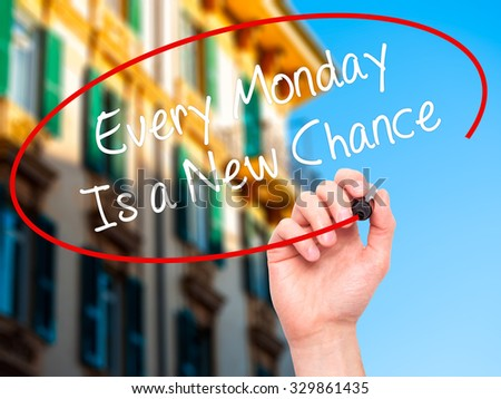 Man Hand writing Every Monday Is a New Chance with black marker on visual screen. Isolated on city. Business, technology, internet concept. Stock Photo - stock photo