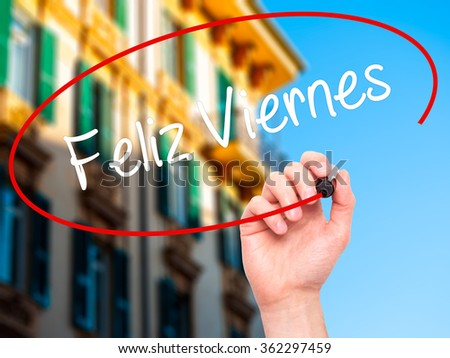 Man Hand writing Feliz Viernes (Happy Friday In Spanish)  with black marker on visual screen. Isolated on background. Business, technology, internet concept. Stock Photo - stock photo