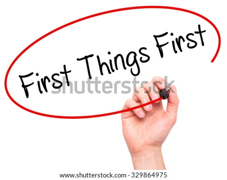 Man Hand writing First Things First with black marker on visual screen. Isolated on white. Business, technology, internet concept. Stock Photo - stock photo