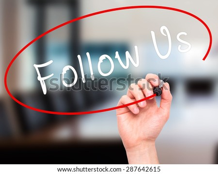 Man Hand writing Follow Us with black marker on visual screen. Isolated on office. Business, technology, internet concept. Stock Image - stock photo