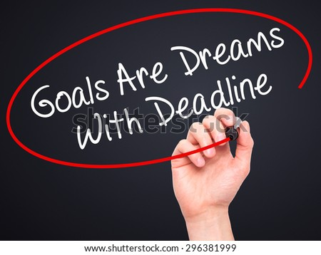 Man Hand writing Goals Are Dreams With Deadline with black marker on visual screen. Isolated on black. Business, technology, internet concept. Stock Photo