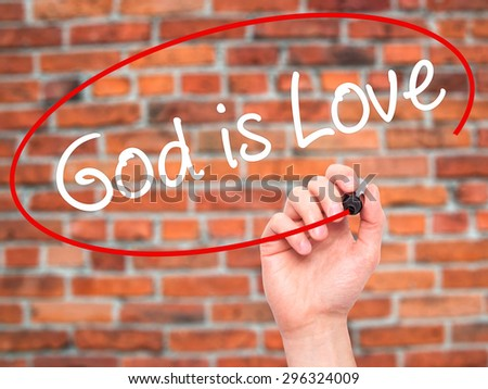 Man Hand writing God is Love with black marker on visual screen. Isolated on bricks. Business, technology, internet concept. Stock Photo - stock photo