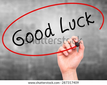 Man Hand writing Good Luck with marker on transparent wipe board. Isolated on grey. Business, internet, technology concept. Stock Photo