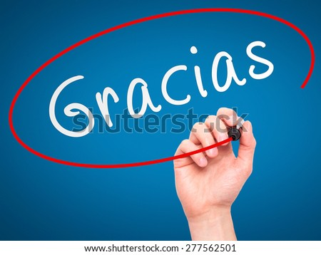 Man Hand writing Gracias with marker on transparent wipe board. Isolated on blue. Business, internet, technology concept.  Stock Photo - stock photo