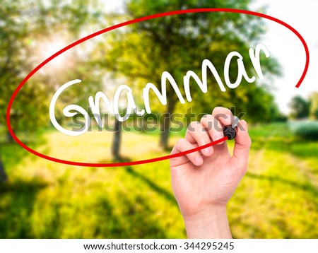 Man Hand writing Grammar with black marker on visual screen. Isolated on background. Business, technology, internet concept. Stock Photo - stock photo