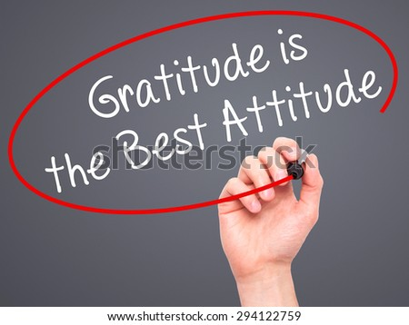 Man Hand writing Gratitude is the Best Attitude with black marker on visual screen. Isolated on grey. Business, technology, internet concept. Stock Photo