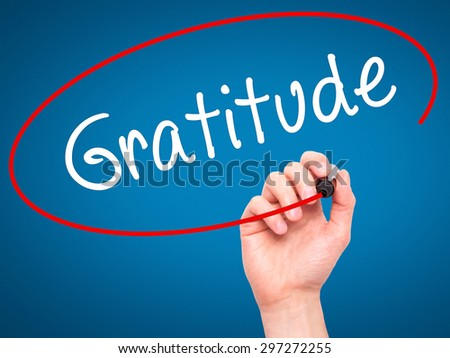 Man Hand writing Gratitude with black marker on visual screen. Isolated on blue. Business, technology, internet concept. Stock Photo - stock photo