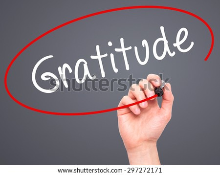 Man Hand writing Gratitude with black marker on visual screen. Isolated on grey. Business, technology, internet concept. Stock Photo - stock photo