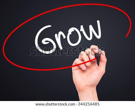 Man Hand writing  Grow with black marker on visual screen. Isolated on background. Business, technology, internet concept. Stock Photo - stock photo