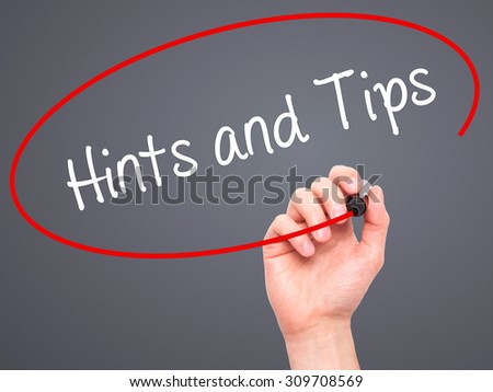 Man Hand writing Hints and Tips with black marker on visual screen. Isolated on grey. Business, technology, internet concept. Stock Photo - stock photo