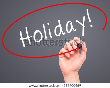 Man Hand writing Holiday! with black marker on visual screen. Isolated on grey. Business, technology, internet concept. Stock Image - stock photo