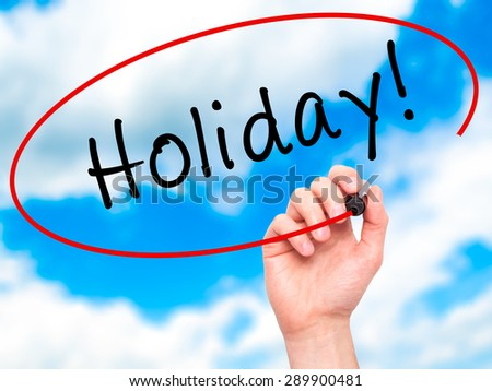Man Hand writing Holiday! with black marker on visual screen. Isolated on sky. Business, technology, internet concept. Stock Image - stock photo