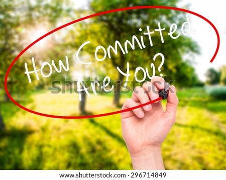 Man Hand writing How Committed Are You? with black marker on visual screen. Isolated on nature. Business, technology, internet concept. Stock Photo - stock photo
