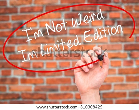 Man Hand writing I'm Not Weird Im Limited Edition with black marker on visual screen. Isolated on bricks. Business, technology, internet concept. Stock Photo - stock photo