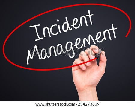 Man Hand writing Incident Management with black marker on visual screen. Isolated on black. Business, technology, internet concept. Stock Photo
