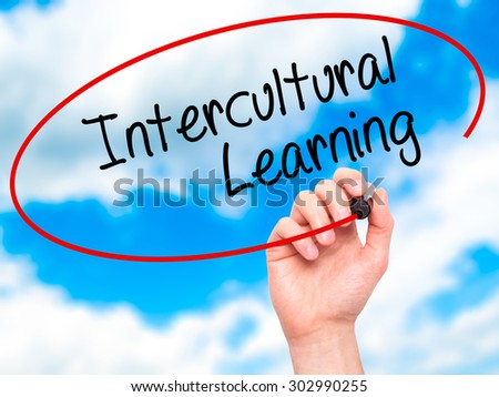 Man Hand writing Intercultural Learning with black marker on visual screen. Isolated on sky. Business, technology, internet concept. Stock Photo - stock photo