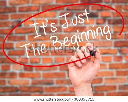 Man Hand writing It's Just The Beginning with black marker on visual screen. Isolated on bricks. Business, technology, internet concept. Stock Photo - stock photo