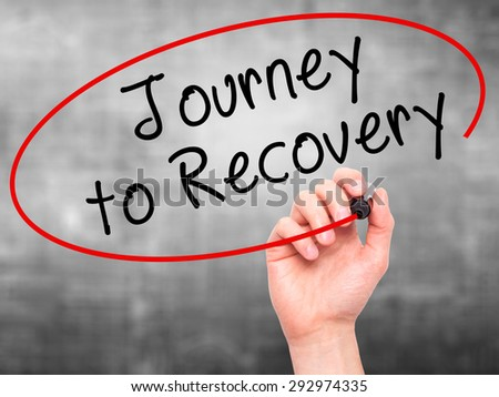 Man Hand writing Journey to Recovery with black marker on visual screen. Isolated on grey. Life, technology, internet concept. Stock Image - stock photo