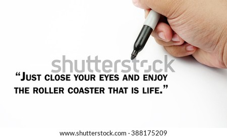 "Man Hand writing ""just close your eyes and enjoy the roller coaster that is life"" with black marker on visual screen. Isolated white background. Business, technology, internet concept. Stock Photo"