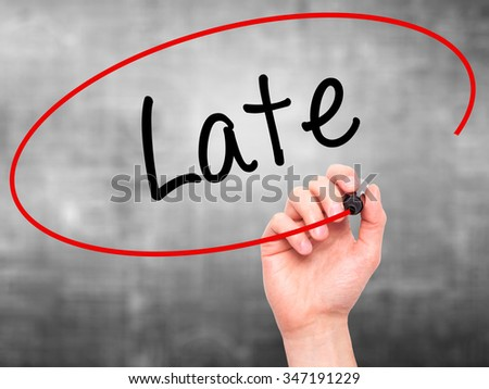 Man Hand writing Late with black marker on visual screen. Isolated on background. Business, technology, internet concept. Stock Photo