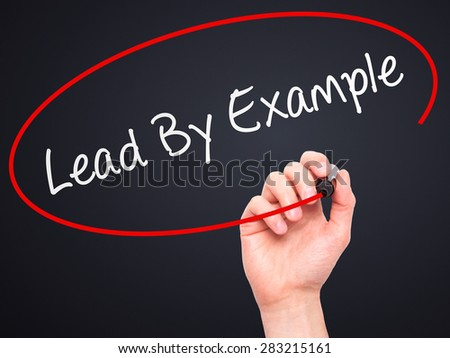 Man Hand writing Lead By Example with marker on transparent wipe board. Isolated on black. Business, internet, technology concept. Stock Photo - stock photo
