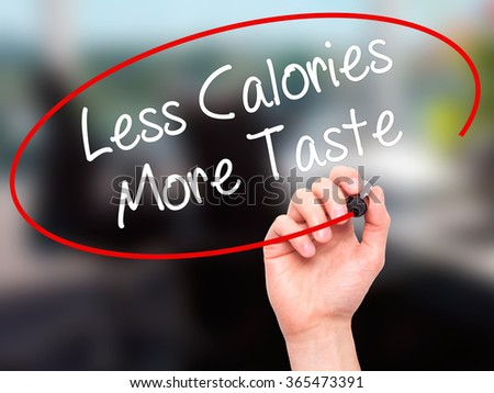 Man Hand writing Less Calories More Taste with black marker on visual screen. Isolated on background. Business, technology, internet concept. Stock Photo - stock photo