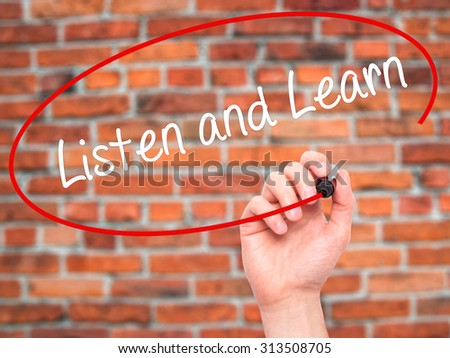 Man Hand writing Listen and Learn with black marker on visual screen. Isolated on bricks. Business, technology, internet concept. Stock Photo - stock photo