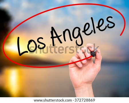 Man Hand writing Los Angeles with black marker on visual screen. Isolated on background. Business, technology, internet concept. Stock Photo - stock photo