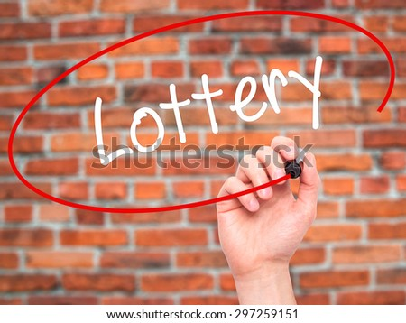 Man Hand writing Lottery  with black marker on visual screen. Isolated on bricks. Business, technology, internet concept. Stock Photo - stock photo