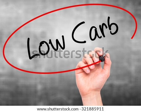 Man Hand writing Low Carb with black marker on visual screen. Isolated on grey. Business, technology, internet concept. - stock photo