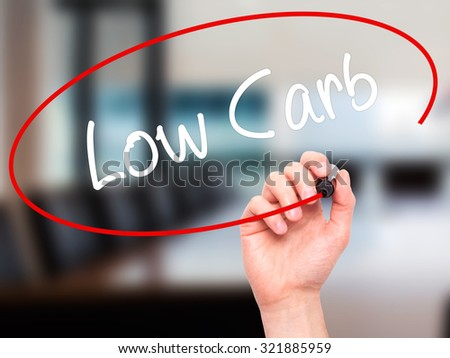 Man Hand writing Low Carb with black marker on visual screen. Isolated on office. Business, technology, internet concept. - stock photo
