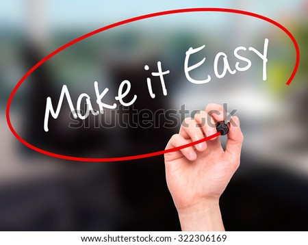 Man Hand writing Make it Easy with black marker on visual screen. Isolated on office. Business, technology, internet concept. Stock Photo - stock photo