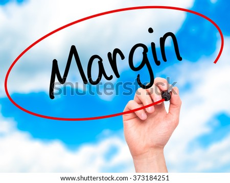 Man Hand writing Margin with black marker on visual screen. Isolated on background. Business, technology, internet concept. Stock Photo