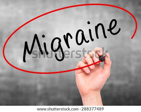 Man Hand writing Migraine with black marker on visual screen. Isolated on grey. Business, technology, internet concept. Stock Image - stock photo