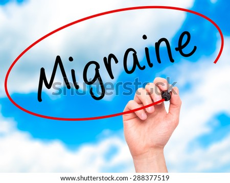 Man Hand writing Migraine with black marker on visual screen. Isolated on sky. Business, technology, internet concept. Stock Image - stock photo