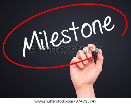 Man Hand writing Milestone with black marker on visual screen. Isolated on background. Business, technology, internet concept. Stock Photo - stock photo