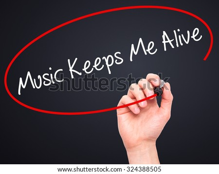 Man Hand writing Music Keeps Me Alive with black marker on visual screen. Isolated on black. Business, technology, internet concept. Stock Photo - stock photo