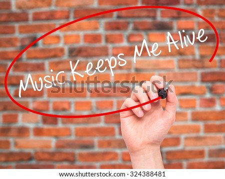 Man Hand writing Music Keeps Me Alive with black marker on visual screen. Isolated on bricks. Business, technology, internet concept. Stock Photo - stock photo