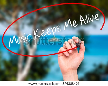 Man Hand writing Music Keeps Me Alive with black marker on visual screen. Isolated on nature. Business, technology, internet concept. Stock Photo - stock photo