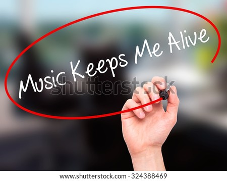 Man Hand writing Music Keeps Me Alive with black marker on visual screen. Isolated on office. Business, technology, internet concept. Stock Photo - stock photo