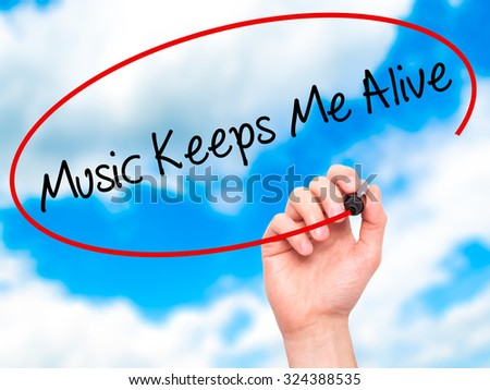 Man Hand writing Music Keeps Me Alive with black marker on visual screen. Isolated on sky. Business, technology, internet concept. Stock Photo - stock photo